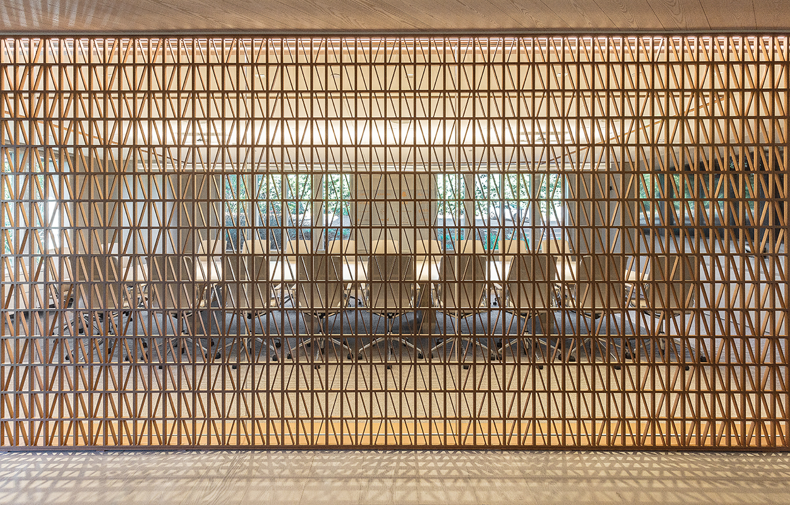 Bronze screens between conference rooms and corridors are backlit to create a play of light and shadow.